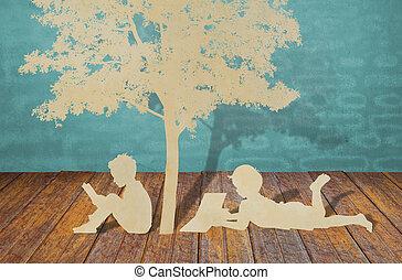 Los niños leen un libro bajo el árbol