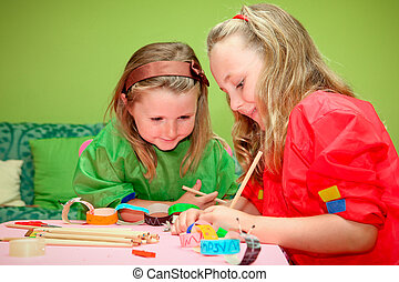 Los niños sonrientes felices dibujando y haciendo artesanías en la escuela de jardín