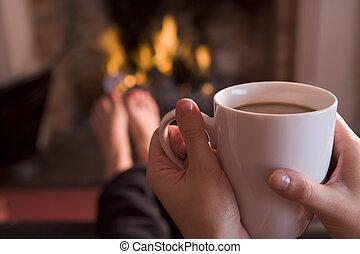 Los pies se calientan en una chimenea con las manos sosteniendo café