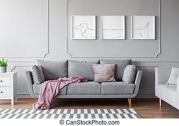 Los posters del perro sobre el cómodo sofá gris en el elegante interior del salón con dos sofás