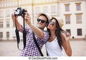 Los turistas felices toman fotos de sí mismos