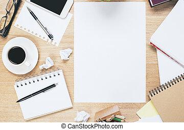 Lugar de trabajo desordenado con hoja de papel en blanco