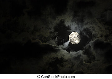 Luna llena y nubes blancas sobre un cielo negro