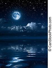 Luna y nubes en la noche en el mar