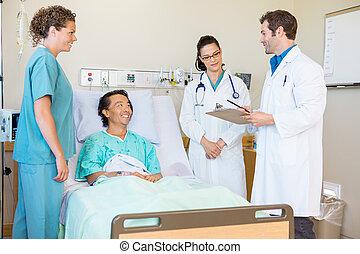 Médicos jóvenes discutiendo notas mientras el paciente feliz y la enfermera los miran en la habitación del hospital