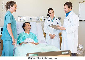 Médicos jóvenes discutiendo notas mientras la enfermera y el paciente los miran en la habitación del hospital