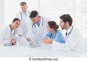 Médicos usando un portátil juntos