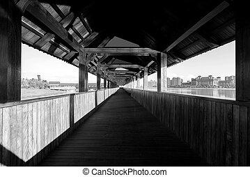 Madera cubierta puente por el río