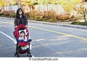 Madre caminando con su hijo discapacitado en cochecitos al aire libre
