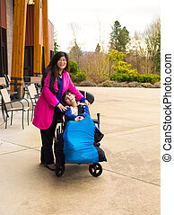 Madre con discapacitado hijo de once años en silla de ruedas al aire libre