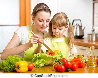 Madre enseñando a hija a mezclar ensalada en la cocina
