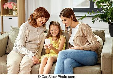 Madre, hija y abuela con smartphone