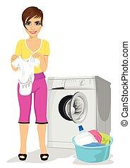 Madre joven sosteniendo chaleco de bebé junto a la lavadora