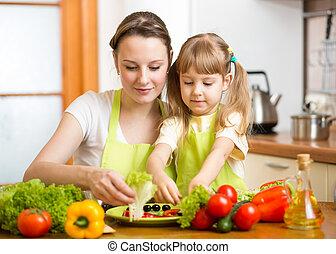 Madre joven y su hijo haciendo ensalada vegetal