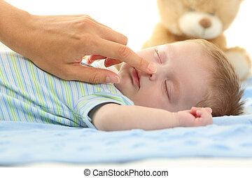 Madre tocando la nariz de un bebé durmiendo