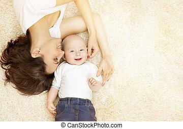 Madre y bebé acostados en la alfombra, feliz retrato familiar, madre con niño, mujer e hijo