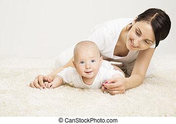 Madre y bebé arrastrándose, niño criado, niño activo y madre feliz tirada en la alfombra