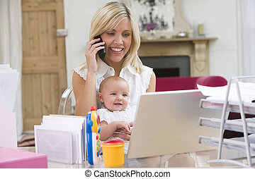 Madre y bebé en la oficina de casa con portátil y teléfono