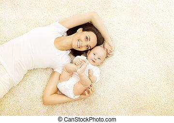 Madre y bebé, feliz retrato de familia, madre con niño en la alfombra, mujer y niño en ropa blanca