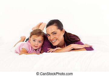 Madre y niña acostadas en la cama