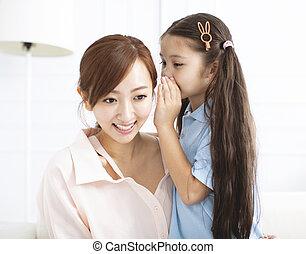 Madre y niña susurrando chismes