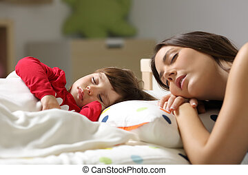 Madre y niño durmiendo en una cama
