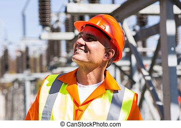 Madura electricista masculino en subestación eléctrica