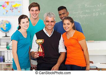 Maestro senior y estudiantes de secundaria con trofeo