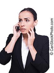 Malas noticias. Una joven frustrada en ropa formal hablando por teléfono móvil y tocándose la cara con la mano mientras estaba aislada en blanco