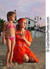 Mamá está sentada en la playa por la noche. Pequeña hija parada cerca. Mamá llevaba un vestido rojo