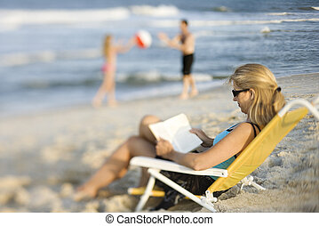Mamá leyendo libros en la playa.