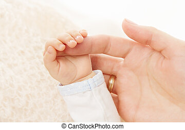 Mano de bebé recién nacido sosteniendo el dedo de padre