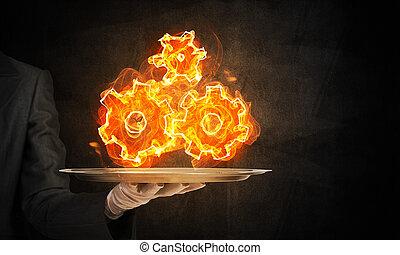Mano de mesera presentando ruedas en llamas.