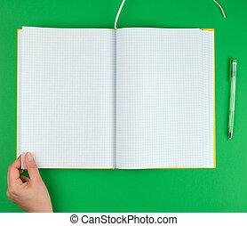 Mano femenina sosteniendo un cuaderno abierto en una celda
