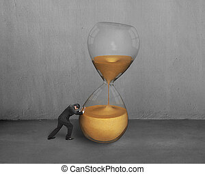 Mano masculina empuja el vidrio de la hora inclinada