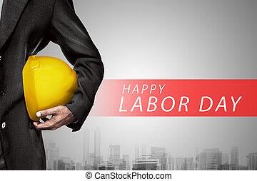 Mano o brazo de ingeniero tienen casco de plástico amarillo para el trabajador