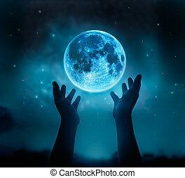 Manos abstractas mientras rezan en la luna llena azul con estrellas en el cielo oscuro, imagen original de la Luna de la NASA.gov