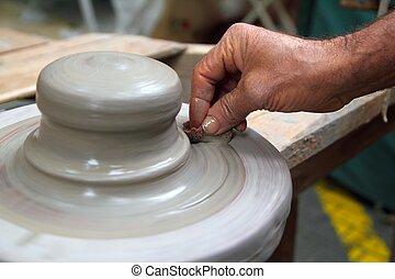 Manos de alfarero trabajando en la rueda de arcilla