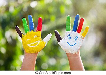 Manos de color con sonrisa pintadas en pinturas coloridas contra fondo de verano verde. El concepto de estilo de vida