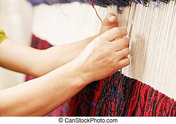 Manos de mujer tejiendo alfombra