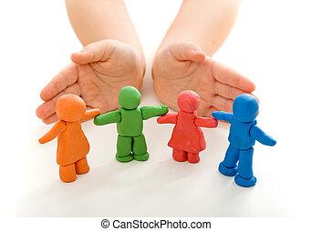 Manos de niño protegiendo a la gente de arcilla