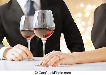 Manos de pareja comprometida con vino tinto en copas
