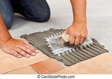 Manos de trabajador extendiendo adhesivo para baldosas de suelo de cerámica