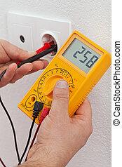 Manos eléctricas midiendo el voltaje en enchufe eléctrico