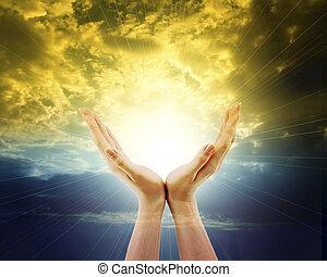 Manos extendidas hacia el sol y el cielo