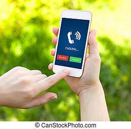 Manos femeninas sosteniendo un teléfono blanco con un tubo de llamada en la pantalla en un fondo de hierba verde