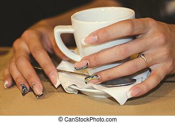 Manos femeninas sosteniendo una taza de café