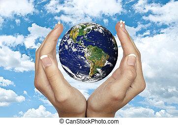 Manos humanas sosteniendo el planeta Tierra contra el cielo azul concepto de protección ambiental