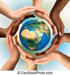 Manos multirraciales que rodean el mundo terrestre