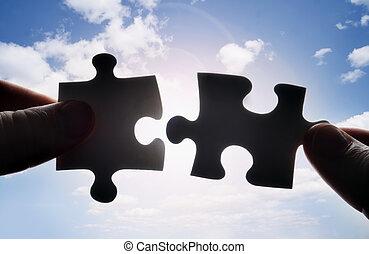 Manos tratando de encajar dos piezas de rompecabezas juntas